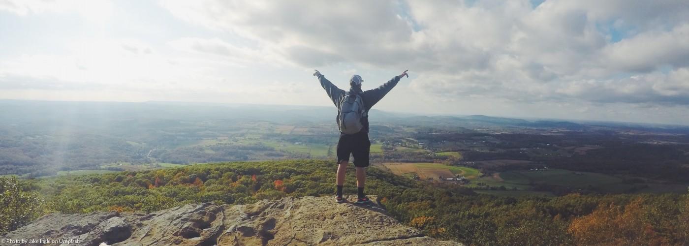 Ein Mann steht auf dem Gipfel eines Berges
